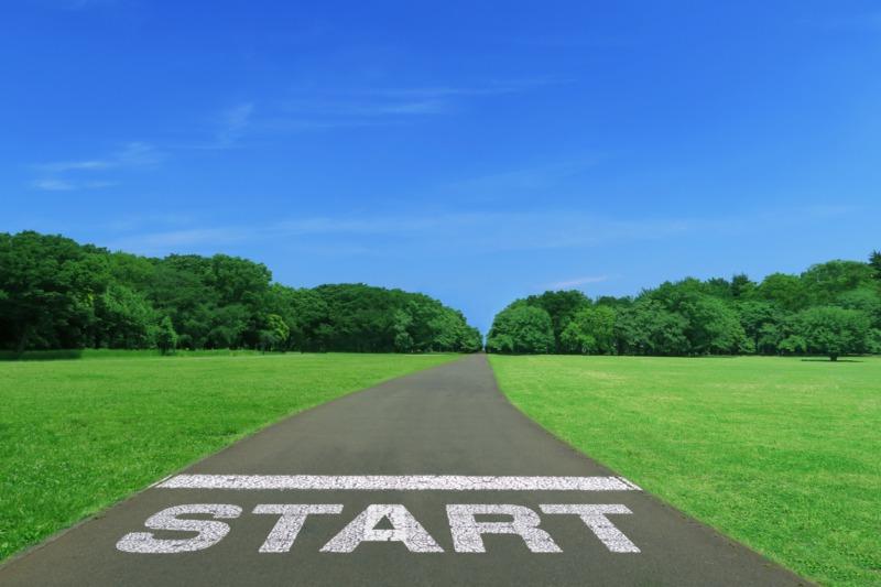 スタート地点が描かれたアスファルトの道-青空と緑の芝生