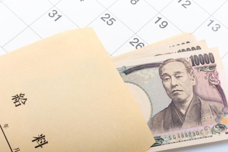 カレンダーと給料袋から覗く一万円札