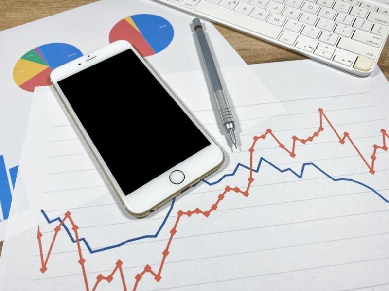 スマートフォンとキーボードとグラフの書類