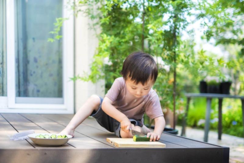 ウッドデッキできゅうりを切る子ども